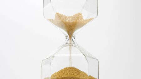 glass sand clock on white with golden balls instead of sand falling. Deadline concept. Stress of time planing concept 写真素材