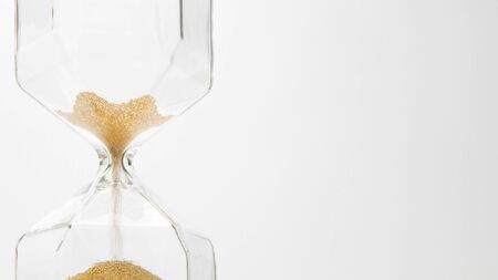 glass sand clock on white with golden balls instead of sand falling Deadline concept that time is ending