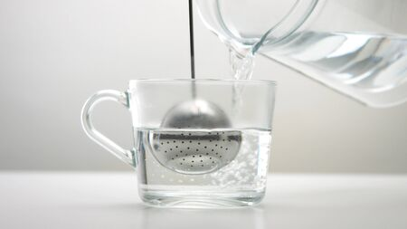 Closeup of transparent cup with brewed tea and a infuser tea spoon Clear hot water pouring into the cup. Half ouf cup is full
