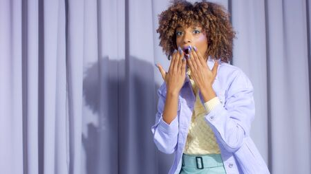 Mixed race black woman with curly hair portrait in pastel tones surprised with eyes wide open and lifted up her hands to mouth wow emotion Banco de Imagens