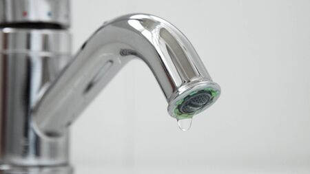 Closeup of a flowing faucet with water drops falling. Moderate consumption concept