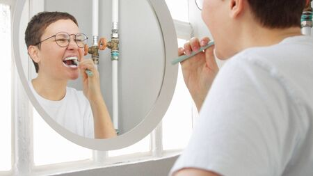 Caucasian woman with a short haircut in front of mirror in bathroom full of sunlight clean her teeth with ultrasonic toothbrush 版權商用圖片 - 144272999