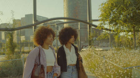 two mixed race black woman with huge afro walking in the park Portrait of talking mixed race women walking Stockfoto