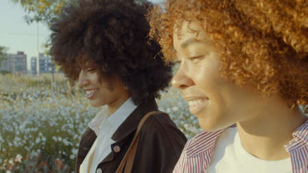 closeup side view portrait of two mixed race black woman walking in the park smiling in morning sunlight Stockfoto