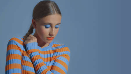 a pretty young model poses and looking down showing eye makeup in blue tones Banque d'images