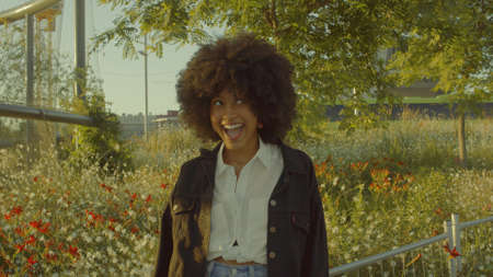 Portrait of mixed race black woman in the park full of flowers. Laughing in contour sunlight Laughing and making faces Cinema film colors