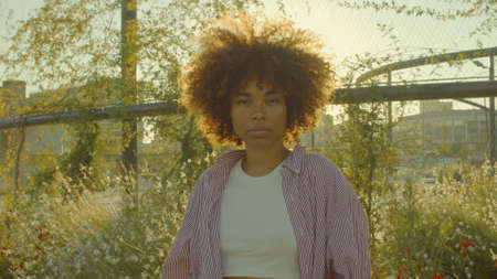 Portrait of mixed race black woman in the park full of flowers with huge afro hair in contour sunlight watching to the camera. Cinema film colors