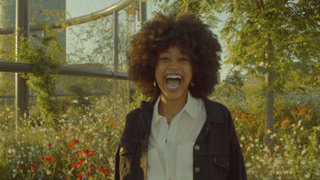 Portrait of mixed race black woman in the park full of flowers. Laughing in contour sunlight laughing . Cinema film colors