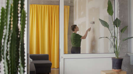 woman alone paint wallboard wall in her room in grey DIY home repair in self-isolation quarantine Stockfoto