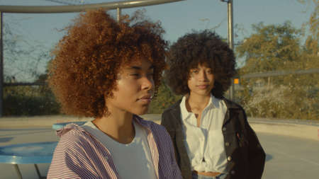 portrait of two mixed race black women in the park at sunrise Natudal light outdoor portrait