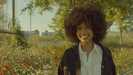 Portrait of mixed race black woman in the park full of flowers. Laughing in contour sunlight and watching the camera. Cinema film colors Archivio Fotografico