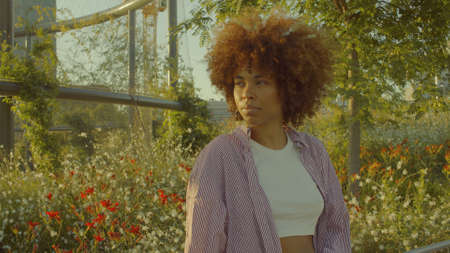 Portrait of mixed race black woman in the park full of flowers with huge afro hair in contour sunlight watching aside . Cinema film colors