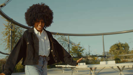 Black woman with huge afro hair and disco-style clothes look Dancing outdoors in tennis park zone in morning light