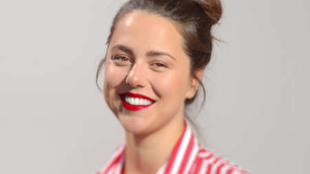 Young attractive dark hair female with vivid red lipstick photo portrait. A lady with brown hair in a bun smiles looking to the camera wide smile showing perfect white teeth. Close-up studio shot