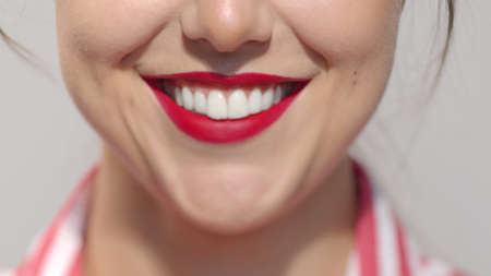 Lips with deep saturated red lipstick close-up. Caucasian brunette girl smiling wide showing crystal white teeth. Anonymous lady studio shot high quality photo image. Archivio Fotografico