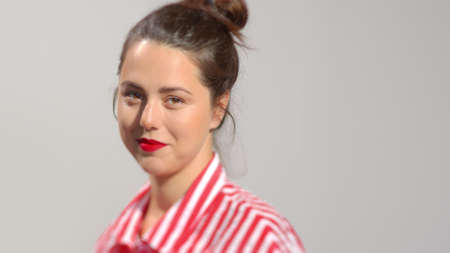Young attractive dark hair female with ruby red lipstick photo portrait. A lady with brown hair in a bun smiles looking to the camera. Studio shot high quality photo image.
