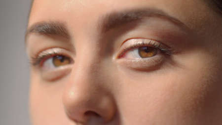 Young woman charming brown eyes with mascara. Look in the camera. Studio shot with dramatic light extreme close-up high quality photo portrait. Archivio Fotografico