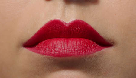 Lips with vivid intense saturated red lipstick extreme close-up. Big puffy lips of a caucasian girl. Anonymous lady studio high quality photo image.
