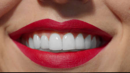 Lips with intense red lipstick close-up. Caucasian girl with plump lips smiling wide showing white perfect teeth. Anonymous lady studio shot slow high quality photo image.