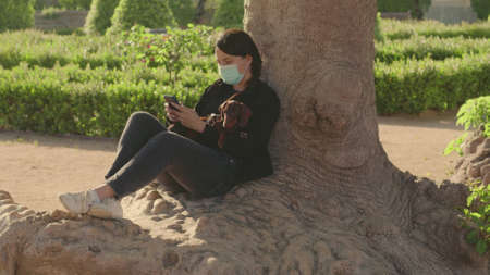 Young dark hair woman is sitting on the base of a tree in the park. Enjoy the moment. Hold and pet chocolate dachshund puppy on knees, navigate on the phone wear the medical mask. High quality photo.