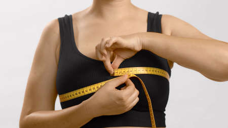 White unrecognizable anonymous lady in black top measures her bust with a tape for bra fitting. Studio no head shot high quality photo image on white background.