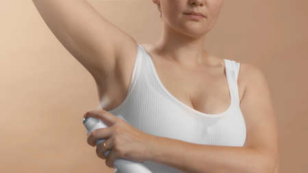 White young european female with lifted hand use antiperspirant to avoid stink and bad smelling. Clean seamless white bra. Studio high quality photo image on beige background.