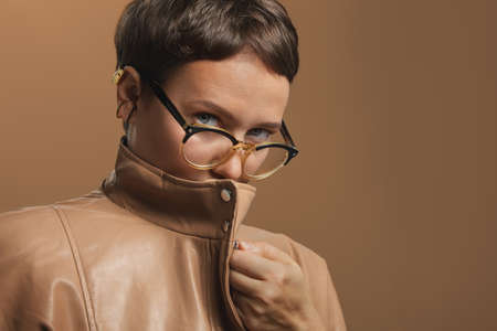 Beautiful and attractive girl with short hair, in the glasses and beige leather jacket. Close zipper and look in the camera with grey eyes. Suspicious and secret concept. Studio medium close up image