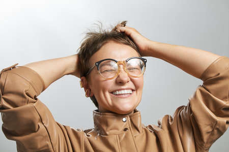 Joyful beautiful lady in glasses with short hair smiling showing teeth and holding her head with hands. Can not believe emotion face expression concept. Studio medium close-up portrait photo image. Archivio Fotografico