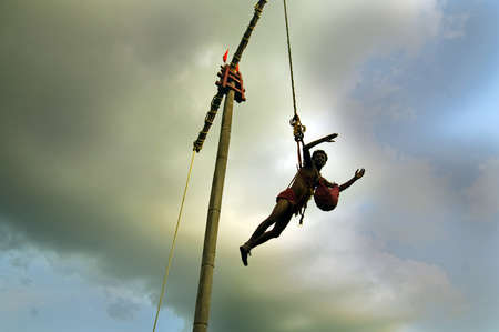 origin of man: A man is flying circularly on a large pillar for his worship. At the time of mid April a festival of Hindu mythology and cultural origin ?GAJAN and CHADAK? is celebrated everywhere particularly in rural Bengal in India.
