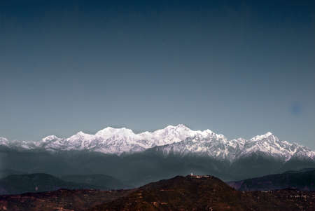 encompasses: A panoramic view of Himalayan Mountain range from Darjeeling, India featuring Kanchenjunga, the third highest mountain in the world and encompasses 16 peaks over 7,000 m (23,000 ft).