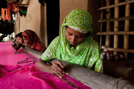 マイクロファイナンス: 2 つの田園インドの女性は、コルカタ、インドの果て手ナイト爵の衣服を作る忙しいです。
