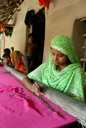 garments: Micro Finance: Two rural Indian women are busy with making hand-knighted garments at outskirts of Kolkata, India.