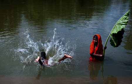 children pond: Jump for Fun: A couple of Indian children are jumping into the pond with playful mood. In India water crisis is a burning issue for society. Particularly in summer, scarcity of water is riches high.