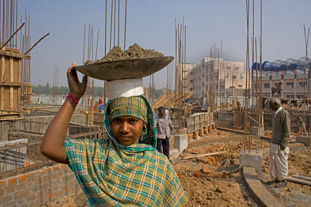 Woman construction worker: An Indian rural woman construction worker is carrying a bucket of material on her head.