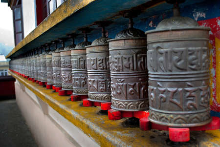 chant: Prayer wheels: A row of Prayer wheels engraved with chant at a Monastery