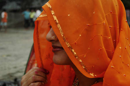 A newly wedded Indian woman wearing a designer sari and ornament keep herself under the veil in India