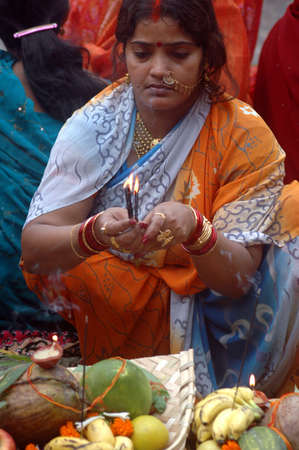 howrah: A women preparing the offerings to the sun god with various fruits, flowers, candles and �agarbattis� on the occasion of chat festival at the bank of river Ganges near the Rabindra Setu (the Howrah Bridge) in Kolkata, India