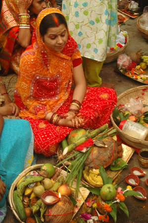 A women preparing the offerings to the sun god with various fruits, flowers, candles and �agarbattis� on the occasion of chat festival at the bank of river Ganges near the Rabindra Setu (the Howrah Bridge) in Kolkata, India