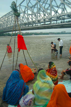 A group of women preparing the offerings to the sun god with various fruits, flowers, candles and �agarbattis� on the occasion of chat festival at the bank of river Ganges near the Rabindra Setu (the Howrah Bridge) in Kolkata, India Editorial