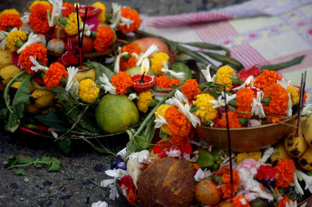 devotee: Preparing the offerings to the sun god with various fruits, flowers, candles and �agarbattis� on the occasion of chat festival at the bank of river Ganges near the Rabindra Setu (the Howrah Bridge)  in Kolkata, India