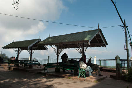 The tourists take a seat on one of the many benches along the periphery, and watch the wonderful views of the mountain peaks and valleys all around the Darjeeling, India. Many elderly tourists indulge as well.� Редакционное