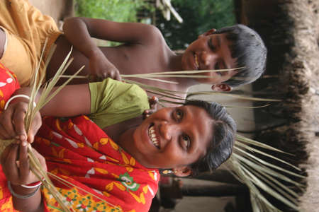 ancestral: A tribal woman is making handicraft from leafs with her child in tribal village near Durgapur, India Editorial