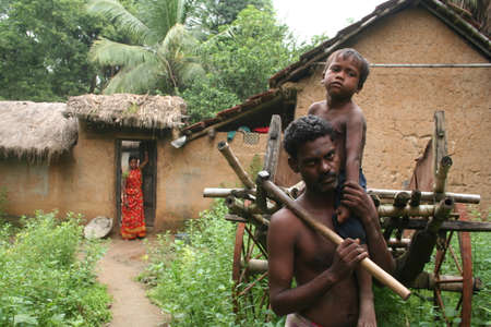 A tribal woodcutter with his son on his solder in front of his house in tribal village near Durgapur, India.