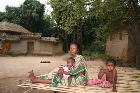 ancestral: Indian tribal children are playing with their grandmother on a handmade bed in front of their house in tribal village near Durgapur, India.