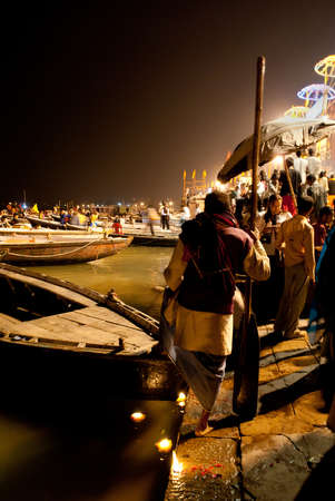 Tourist boats are waiting at the river bank and boatman and local people are waiting for tourists at Varanasi, India Tourists are watching the Puja Ceremony of the Ganges River from boats on river. Editorial