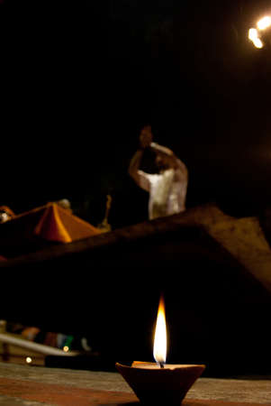 sanskrit: A hindu brahmin priest blows on a conch shell leading a night puja prayer ceremony on the Ganges river ghats in Varanasi, India. Editorial