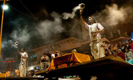 sacrifices: A Hindu Brahmin priest is leading a night prayer ceremony on the Ganges River Ghats in Varanasi, India.