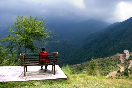 A tourist is enjoying the beauty of nature, sitting on a bench at the top view point of hill station Dharamsala , Himachal Pradesh, India. It's a bright sunny day in the hill station and tourists enjoy the natural beauty of mountains in cool weather. Ever