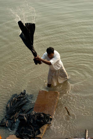 Washing clothes at Raja Ghat, Varanasi, in the holy river Ganages. Editorial