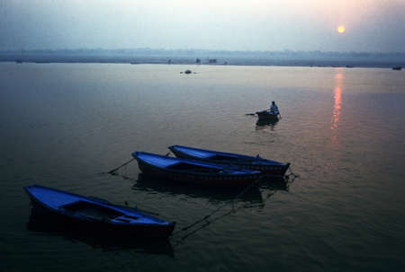 It is a Sunrise at Benaras or Varanasi on river Ganges. It declares the beginning of a new day. First boat starts on its way although other waits for their turn, but it is sure that it will be any time, because a new morning call them to wake up.